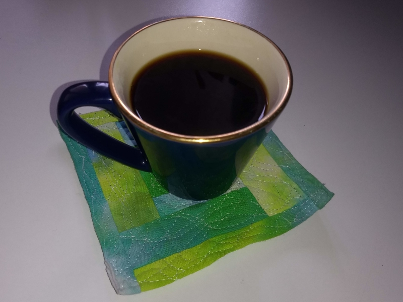 Funky green, white and yellow mini quilt coaster with a cup of black coffee on it