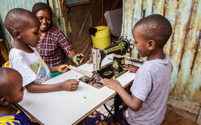 Black children and a women around an old-fashioned sewing machine