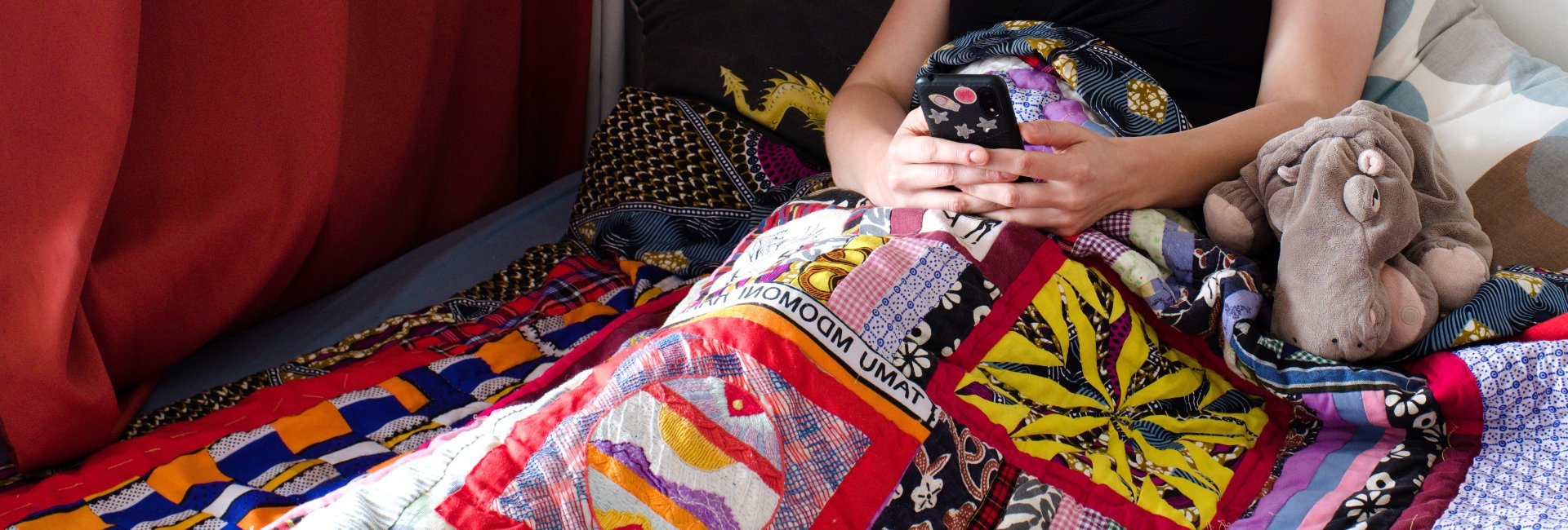 Rianne of Kick-Ass Quilts laying under her Kenyan quilt relaxing with her phone.