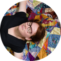Rianne of kick-ass quilts relaxing on a crazy patchwork picknick quilt made with upcycled fabric
