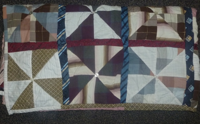 Quilt made with men shirts and ties in brown, red, blue and white colours finishing with tying technique