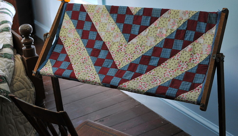 Hand quilting frame used by the amish with a red, blue and white nine patch quilt in it