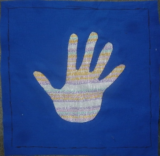 Quilt block of a hand with a blue background made with the reverse applique technique