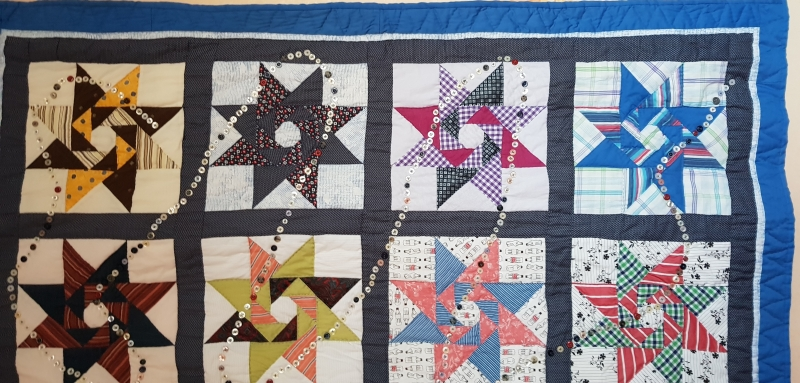 Revolving star quilt by Karin Doller made with fabrics from shirts of family members. Blue, yellow, white and pink