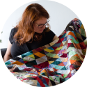 Rianne of kick-ass quilts looking at her first quilt made with donated scrap fabrics and old clothes