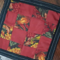 Rita Bailey mini-quilt coaster  made in a nine patch pattern with a combination of red solid fabrics and fabric with autumn leaves