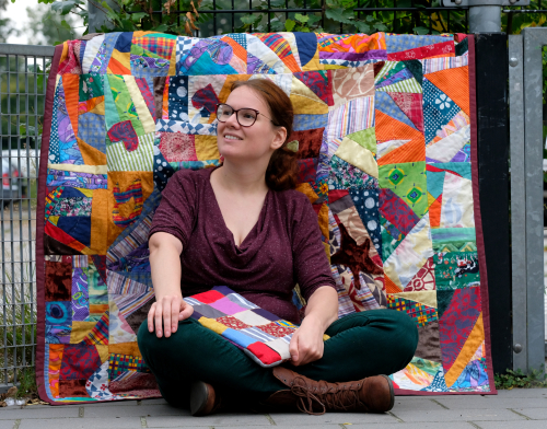 Quilter Rianne sitting croslegged with a colourful crazy quilt as backdrop and a quilted laptop sleeve on her lap