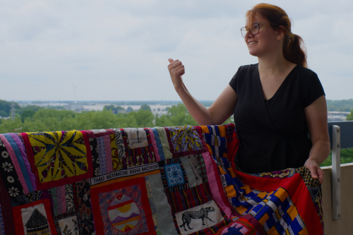 Rianne from Kick-Ass Quilts pointing to Kenya the distance with a colourful quilt made with Kitenge Kenyan fabrics