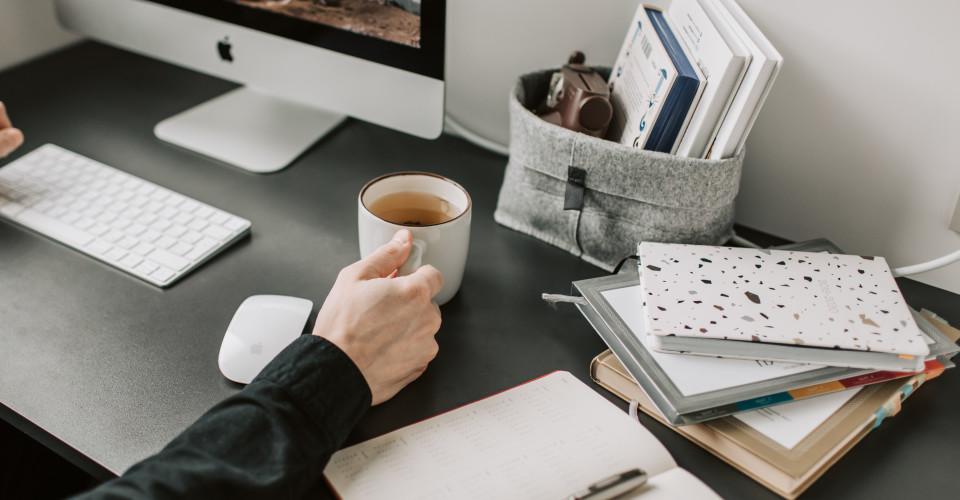 Man zittend achter een bureau met computer en pen en papier, die een kop thee vast houdt