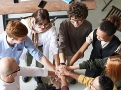 Team houdt handen op elkaar, staan in een cirkel bij een bureau