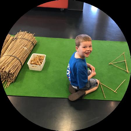 Een jongen maakt een begin met het bouwen van een piramide van bamboestokken voor de bamboetoren