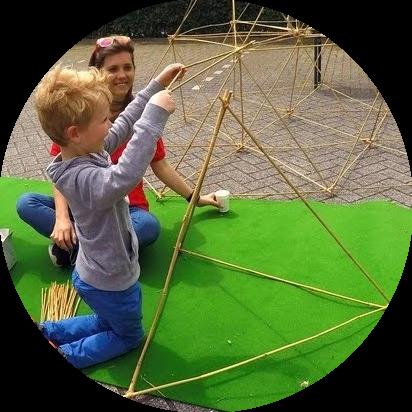 Een jongen bouwt een piramide van bamboestokken onder begeleiding van een instructrice