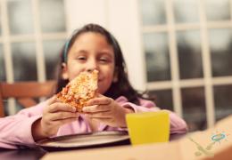 Kookcollege kinderfeestje kind geniet van zelf gebakken pizza