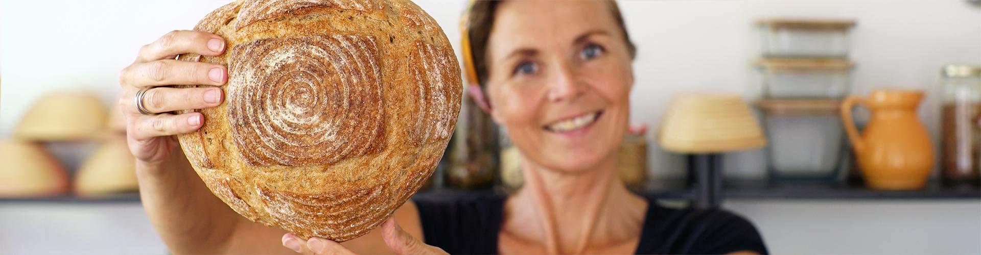 Marije Bakt Brood lacht met ambachtelijk brood voor zich uit gestoken in bakkers keuken met potjes