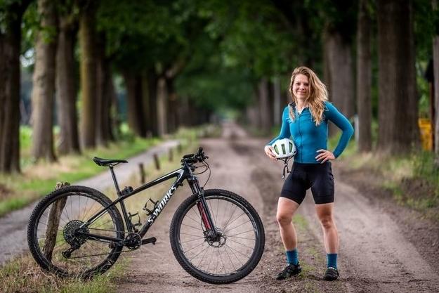 vrouw met wielrenfiets in bossen