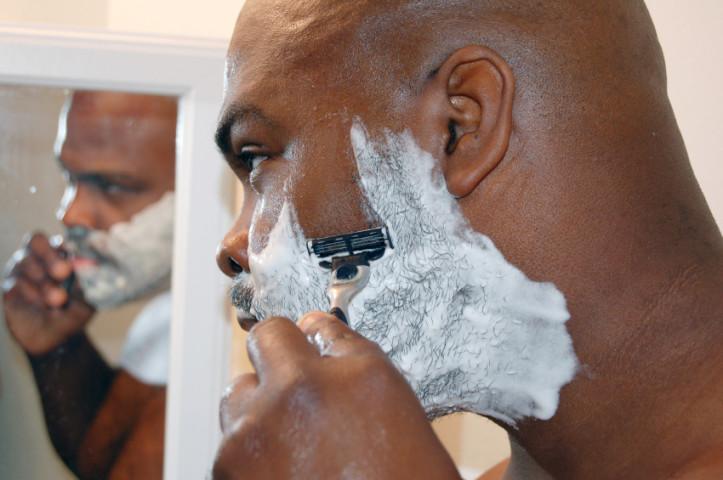 Donkere man scheert baard