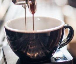 zwart-wit kopje wordt gevuld op koffiemachine