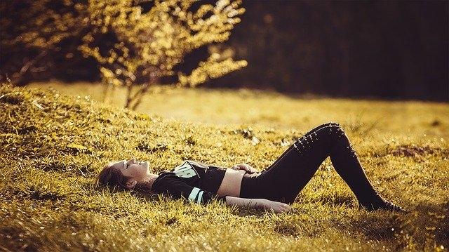 Meisje ligt op het gras te ontspannen