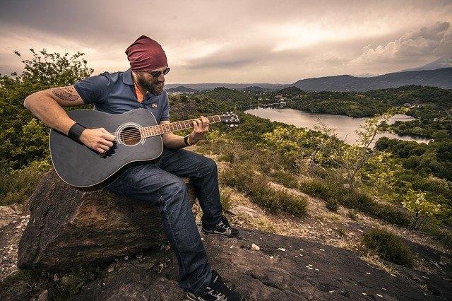 Man speelt gitaar in vrije natuur