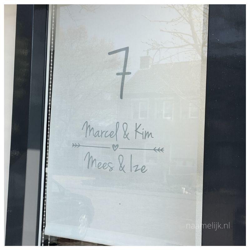 Huisnummer sticker speels in grijs, maat L op het raam van de voordeur