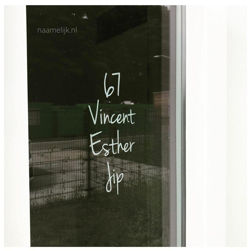 Huisnummer speels in gebroken wit, maat M op het raam bij de voordeur