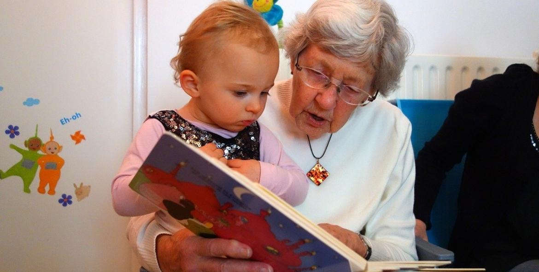 Oma leest een kindje voor uit een prentenboek