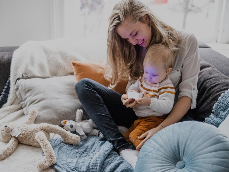 Een baby zit op schoot bij zijn moeder terwijl ze samen naar een Numsy white noise machine kijken