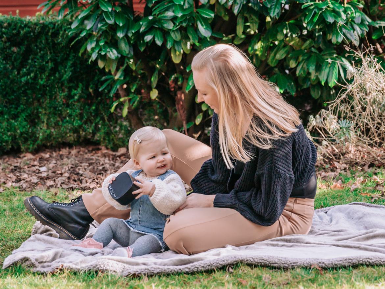 Een moeder zit met haar dochter op een kleedje buiten. Het kindje heeft een Numsy white niose machine vast