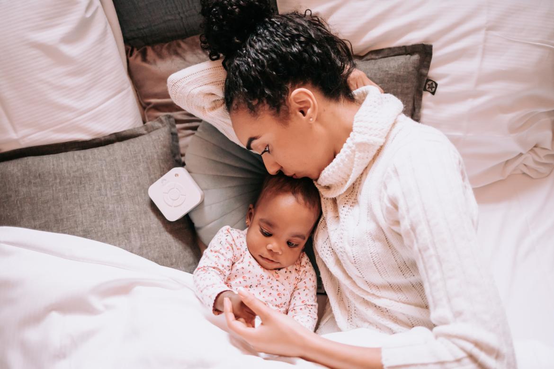 Vrouw met kindje in bed, daarnaast ligt een Numsy White Noise machine