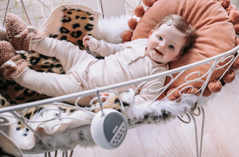 Baby ligt in een wieg met een Numsy white noise machine erbij