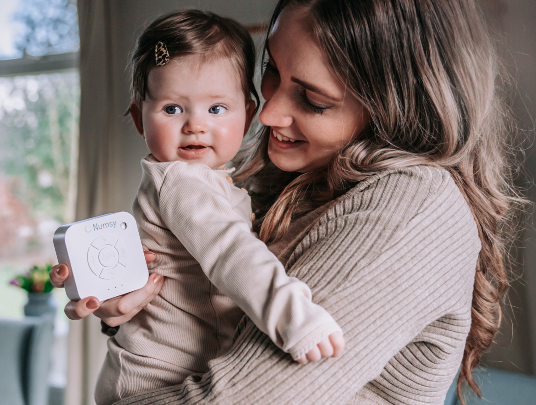 Moeder draagt haar kindje terwijl ze een white noise machine vast heeft.