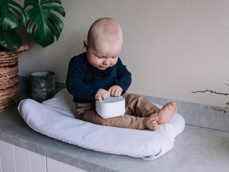 Kindje zit op een kussentje en speelt met een Numsy white noise machine