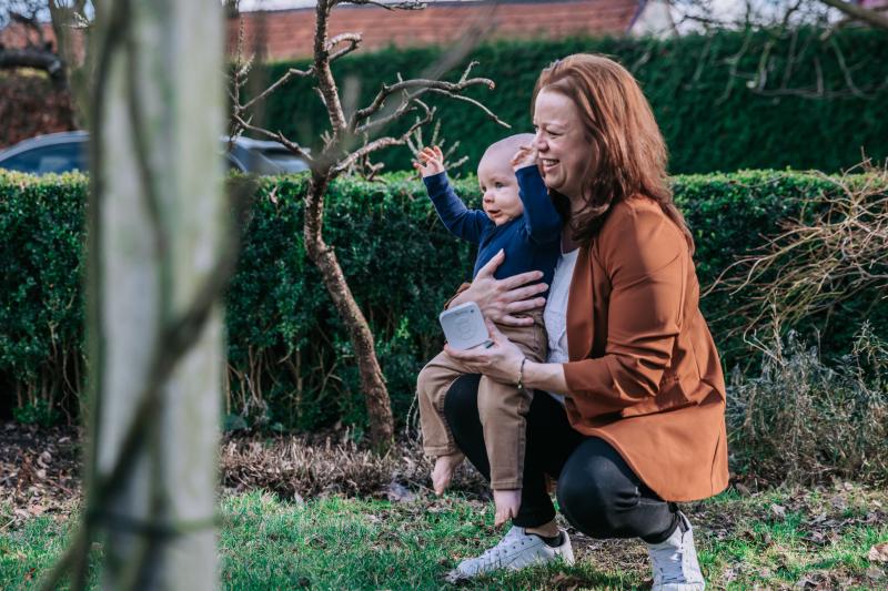 Vrouw met baby en Numsy white noise machine buiten in de tuin