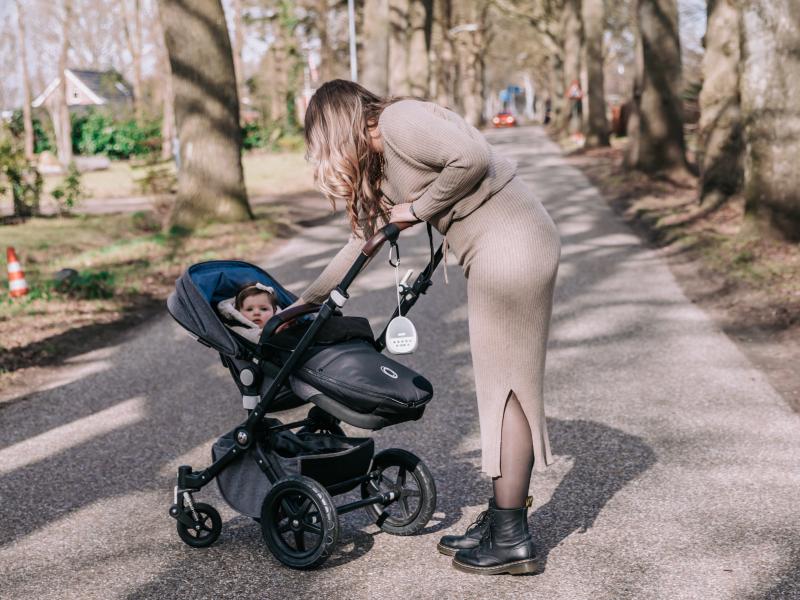 Moeder wandelt met haar dochter in de wandelwagen