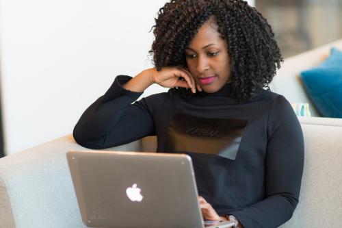 Vrouw leest op haar laptop.