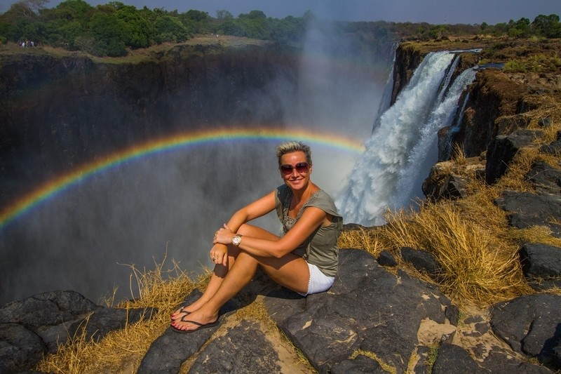 In front of the mighty Victoria Falls in Zambia with a perfect rainbow
