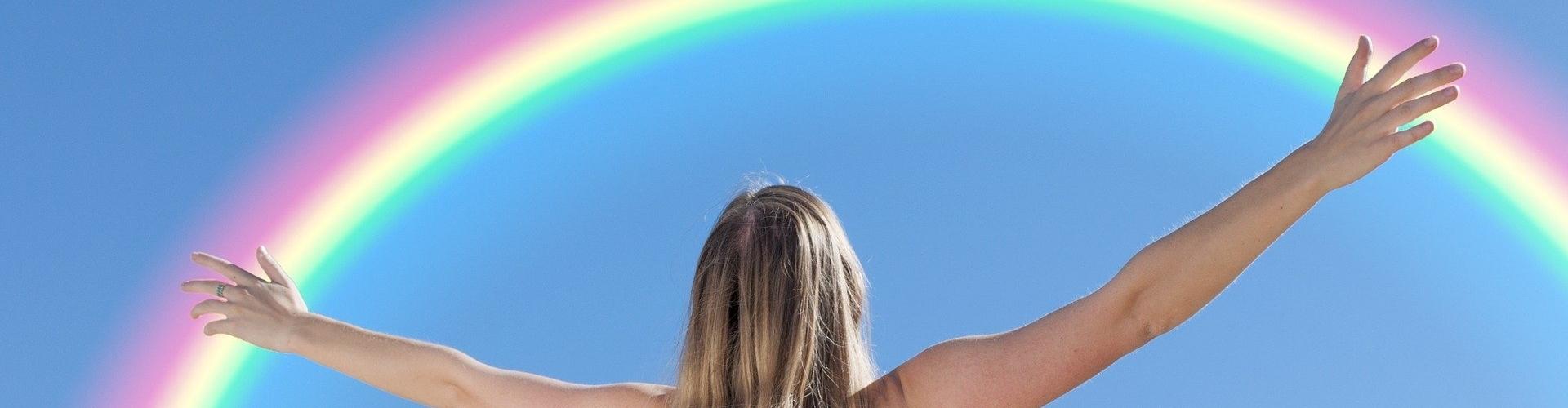Vrouw in wit hemd voor een blauwe lucht met een regenboog