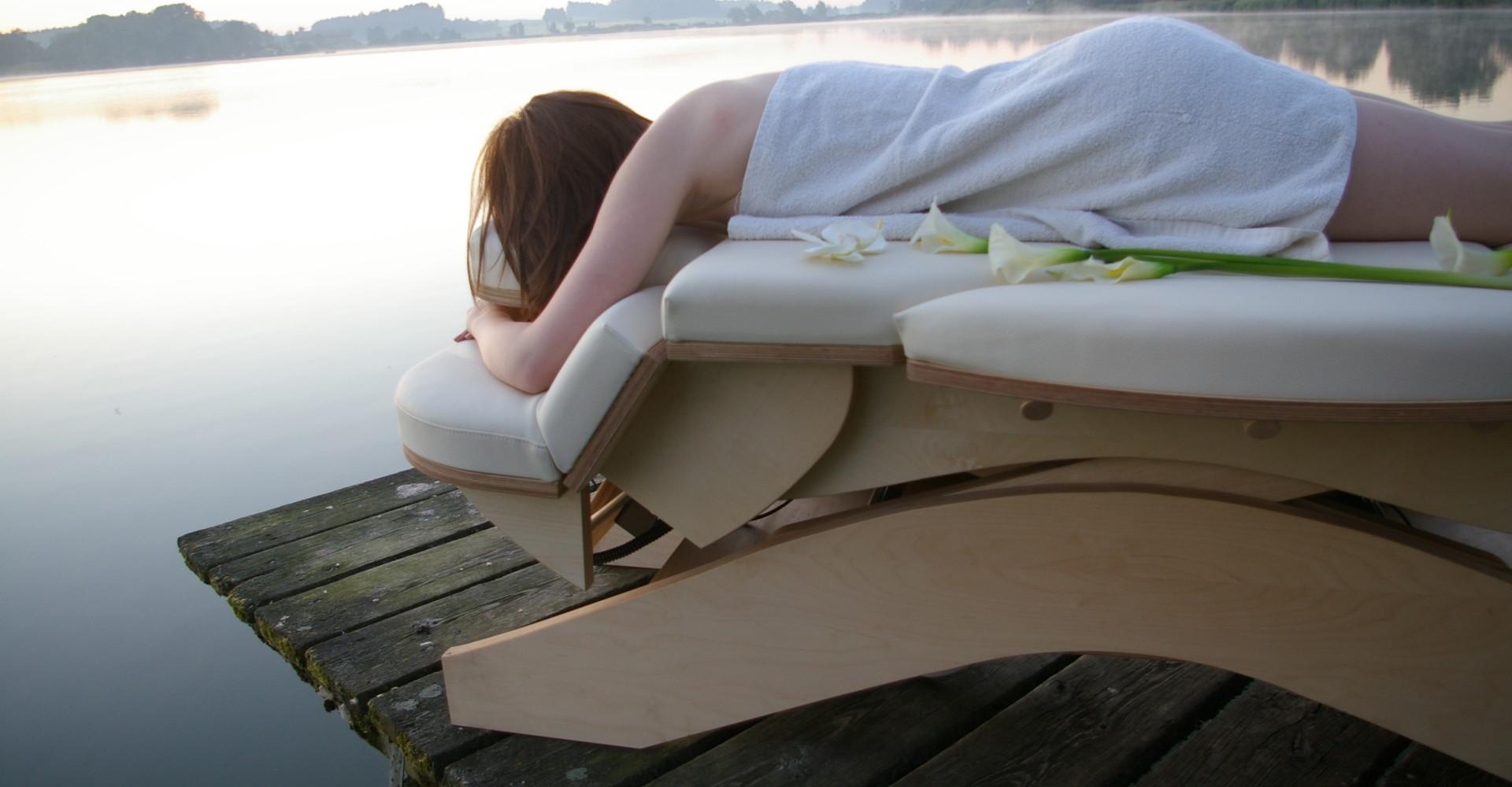 Vrouw op massagetafel bij steiger aan meer