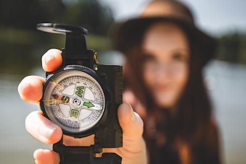 jonge vrouw die kompas vasthoudt
