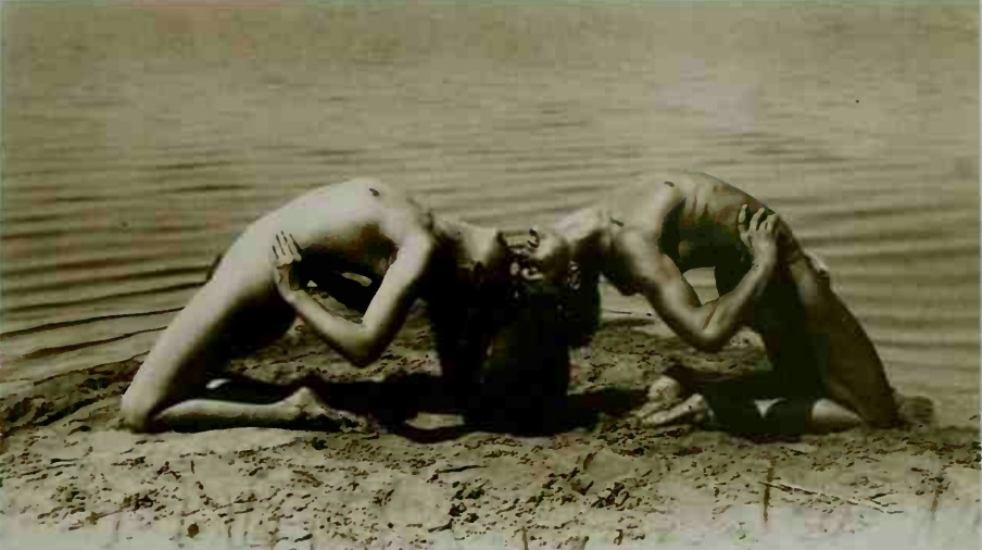nudes at the beach in an acrobatic pose