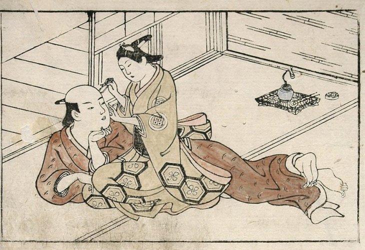 Young boy picks the ear of an older manby Ishikawa Toyonobu