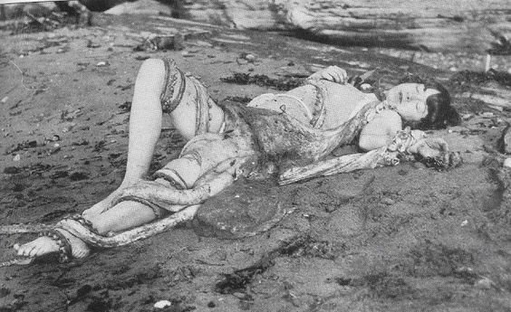 tentacle erotica - black and white photograph of an Asian girl lying on the beach with an octopus on top of her