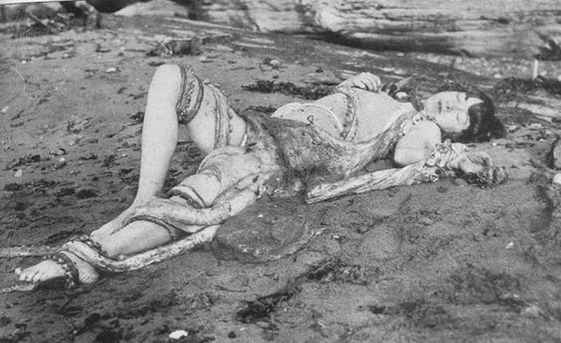 black an white photo of a girl lying on the beach with an octopus on top of her
