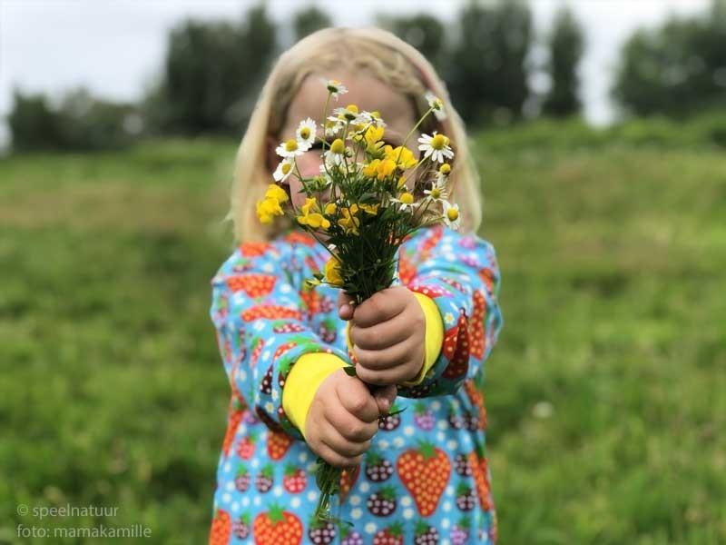 kind met zelf geplukte bos bloemen