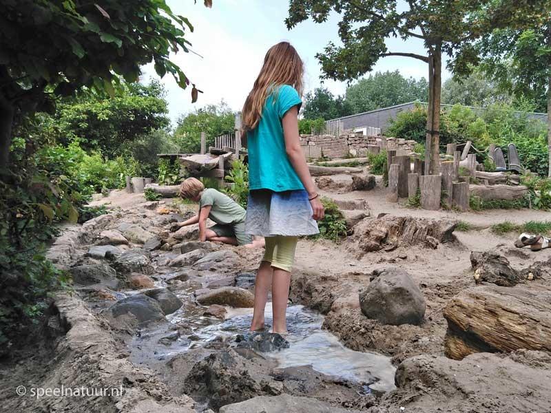 spelen met water en zand op groen schoolplein