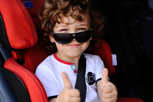 Jongen in de wagen in rode kinderstoel met zonnebril en steekt zijn duimpjes omhoog