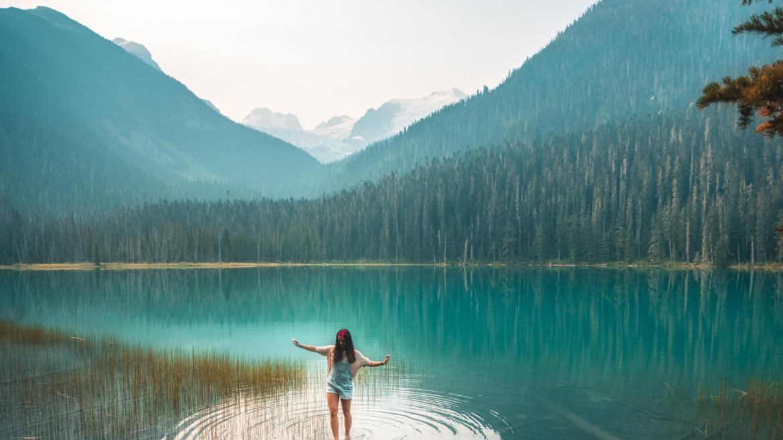 vrouw die in koud water staat in een bergachtig landschap