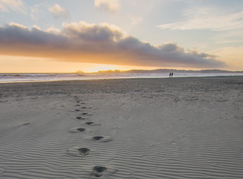 Voetstappen op het strand en 2 mensen die mindful aan het wandelen zijn