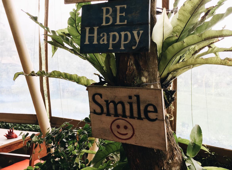 Houten bord in een tropisch oord met het woord 'smile' (glimlach) erop.