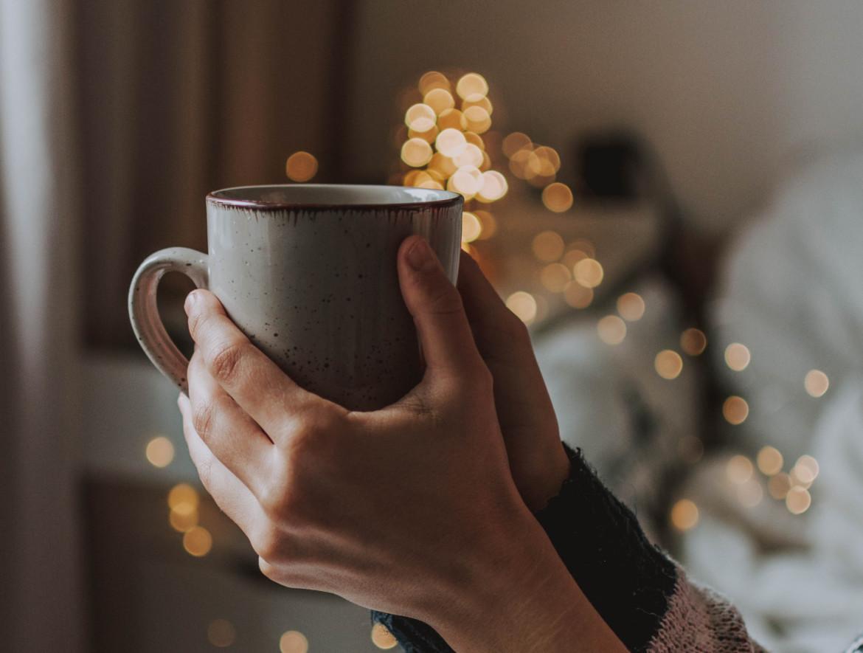 Iemand die mindful een kop koffie vasthoudt